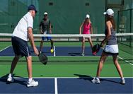 Four People Playing Pickleball on a Court